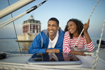 Smiling young couple hanging out on a boat.