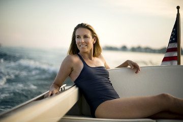 Happy middle aged woman relaxing on a boat.