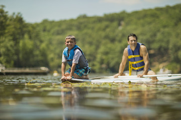 Father and son having fun paddleboarding on the river.