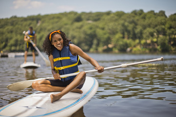 Portrait of a smiling young woman sitting on a paddleboard.