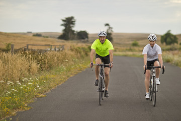 Portrait of a happy mature couple cycling along a country road.