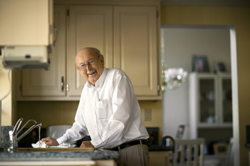 Smiling elderly man cleans up in the kitchen after lunch.