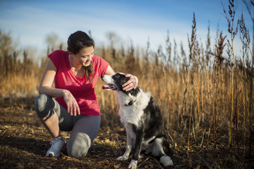Smiling young woman kneels and pets her dog as they prepare to go for a run in the countryside.