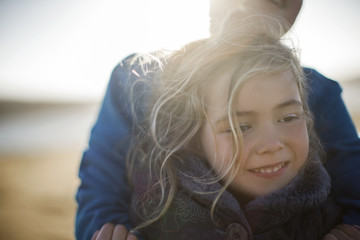 Smiling young girl wrapped in a blanket is held safe and warm in her daddy's arms.
