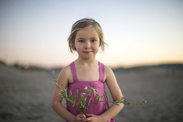 Portrait of a sweet young girl holding a bunch of wildflowers on the beach at dawn.
