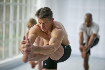 Focused mature man holding his foot during a yoga class.