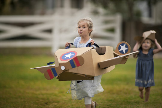 Two little girls have fun playing with cardboard box airplanes on the lawn.