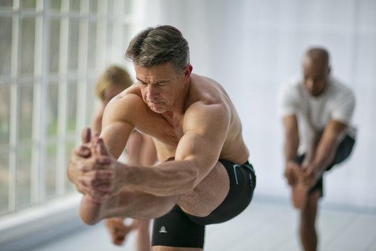 Man practicing yoga in gym