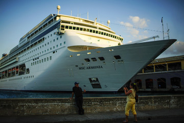People take pictures in front of the cruise ship MSC Harmonia in Havana, Cuba
