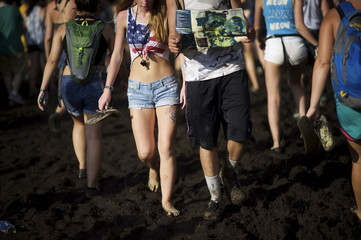 Revelers walk through a muddy path during the Firefly Music Festival in Dover