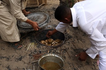 Workers of a small hotel cook chicken in a traditional way called 'abu mardam' in Siwa