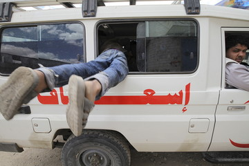 A boy enters through the window of a Yemen Red Crescent vehicle taking displaced people to a another safe shelter in Sanaa