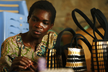 A woman makes hand bags using beads at the Uzima bead-making workshop in Nairobi