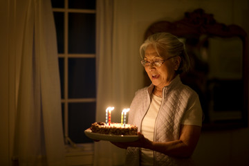 Senior woman holding a birthday cake decorated with birthday candles.