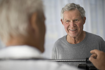 Smiling mature man watches his doctor set up scales before a medical examination.