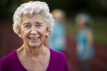 Portrait of a smiling senior woman on an athletic track.