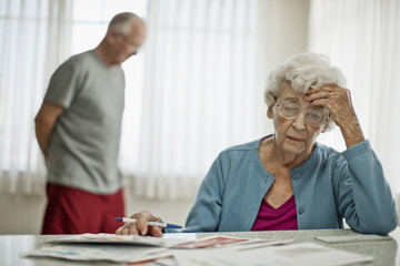 Anxious elderly couple worry about how they will pay all the bills they have received.