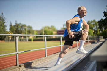 Senior man stretching before a race at a sports track.