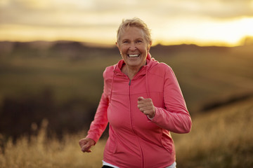 Portrait of a smiling mature woman jogging at sunset.