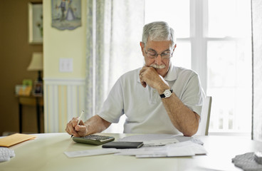 Stressed senior man calculating his home finances.