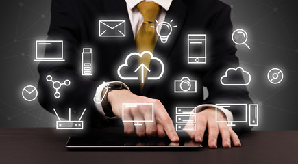 Businessman in suit typing with multimedia concept