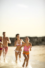 Family running together on a beach.
