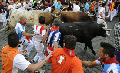 Runners sprint alongside a Fuente Ymbro fighting bull at Telefonica corner during the fifth running of the bulls at the San Fermin festival in Pamplona