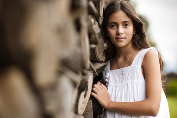Portrait of girl leaning against stack of firewood