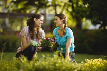 Two women smile and talk as they sit and kneel on the ground ready to plant flowers.