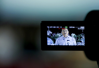 Malaysia's Defence Minister and acting Transport Minister Hussein is seen on the viewfinder of a video camera as he speaks at a news conference in Kuala Lumpur