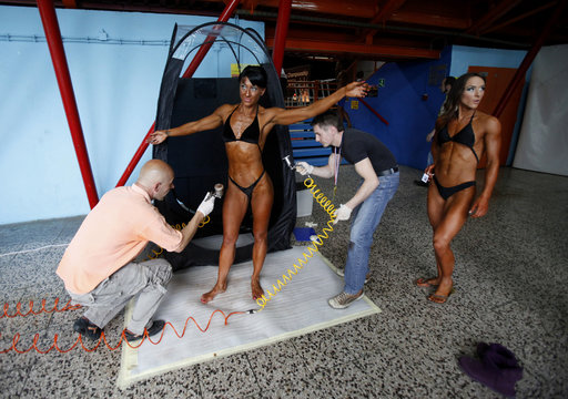 A participant has tanning lotion applied on his body during the European bodybuilding competition in the Zagreb