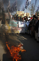 Supporters of Jamaat-ud-Dawa Islamic organization shout slogans while Indian national flag burns during a demonstration in Lahore