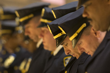 New York Police Department officers bow their heads during a promotions ceremony at Police Headquarters in New York