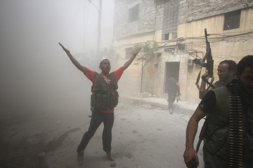 Free Syrian Army fighters gesture during fighting with Syrian government forces in the El Amreeyeh neighborhood of Aleppo