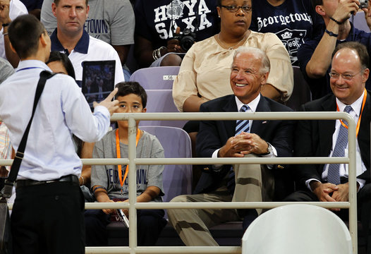 Joe Biden smiles as a Chinese man uses a tablet computer to take his picture at a U.S.-China friendship basketball match held at the Olympics sports center in Beijing
