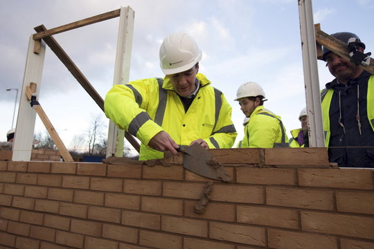 Britain's Chancellor of the Exchequer George Osborne lays a brick during a visit to a housing development in South Ockendon in Essex, Britain