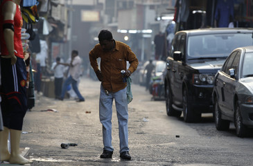 A man recovers from tear gas during a demonstration in capital Manama