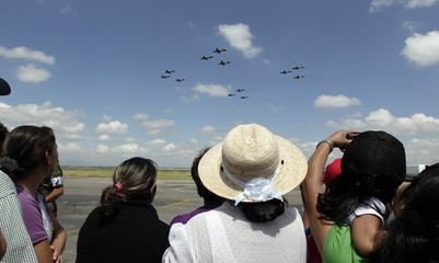 People watch as Pilatus PC-7 aircrafts fly in formation during the air show at the military airport in Santa Lucia near Mexico City