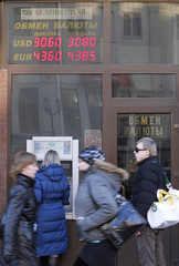 Woman uses a cash dispenser, with a board showing currency exchange rates above her, in Minsk