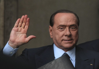 Italy's former PM Berlusconi waves as he arrives at the lower house of parliament in Rome