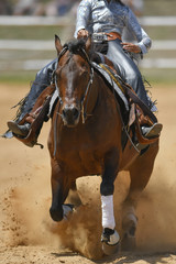 The front view of a rider in cowboy chaps and boots sliding the horse in the sand