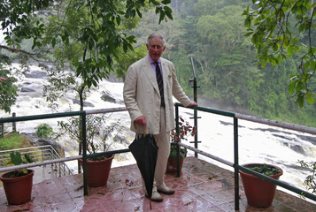 Britain's Prince Charles poses for pictures against the backdrop of Vazhachal waterfalls at Thrissur district in Kerala