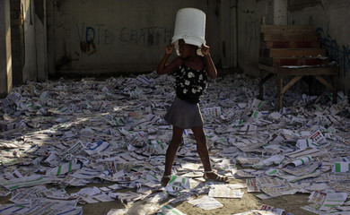 A girl walks over electoral materials lying out on the floor after angry voters trashed the voting center on Sunday in Port-au-Prince