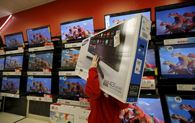 A worker carries a television for a customer who made a purchase during Black Friday Shopping at a Target store in Chicago