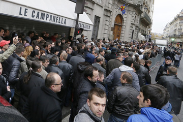 Romanians wait in line to enter a polling station at the Romanian embassy in Paris