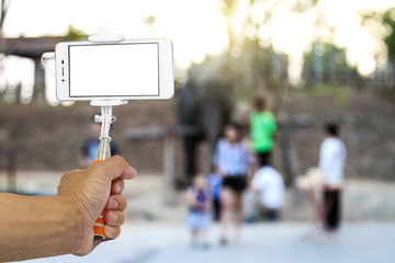 Smart phone on a selfie stick with hand at a zoo. Blank screen with copy space