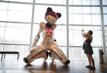 A woman photographs 'Super Space Titan Kitty' by Colin Christian at the 'Hello! Exploring the Supercute World of Hello Kitty' museum exhibit in honor of Hello Kitty's 40th anniversary, at the Japanese American National Museum in Los Angeles