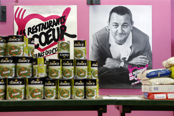 "Canned food and packages of rice are displayed in front of a picture of late French comic Coluche at a food distribution centre for the ""Les Restos du Coeur"" (Restaurants of the Heart) in Paris"