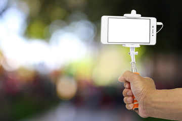 Smart phone on a selfie stick with hand. Blank screen with copy space