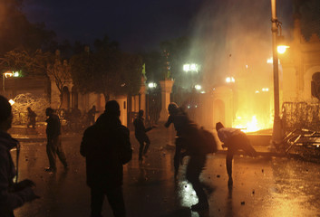 Protesters throw stones at security forces inside the presidential palace during clashes between protesters and police in front of the palace, in Cairo